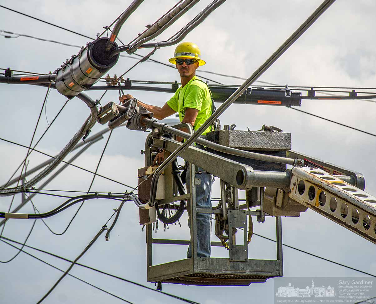 A contractor pulls fiber optic cable along utility poles through Uptown Westerville along North State Street to a nearby business upgrading their data connectivity. My Final Photo for April 26, 2016.