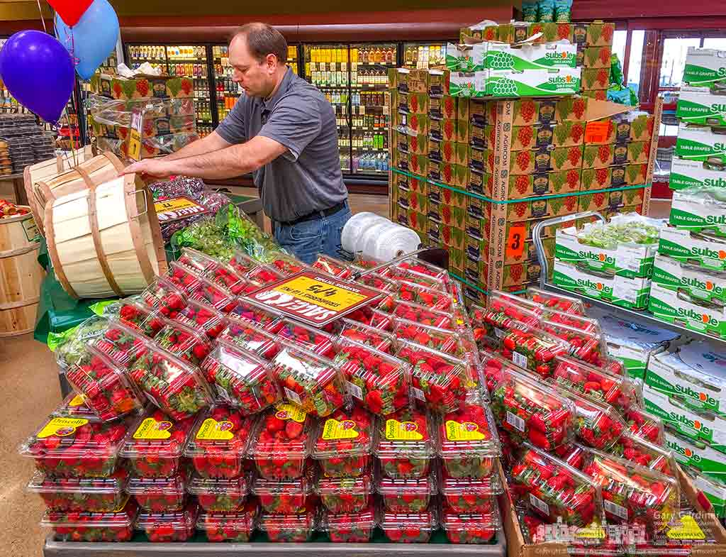 A grocer arranges fresh strawberries and green grapes just inside the entrance to Fresh Thyme as the new grocery store in Westerville prepares for its grand opening Wednesday. My Final Photo for April 5, 2016.