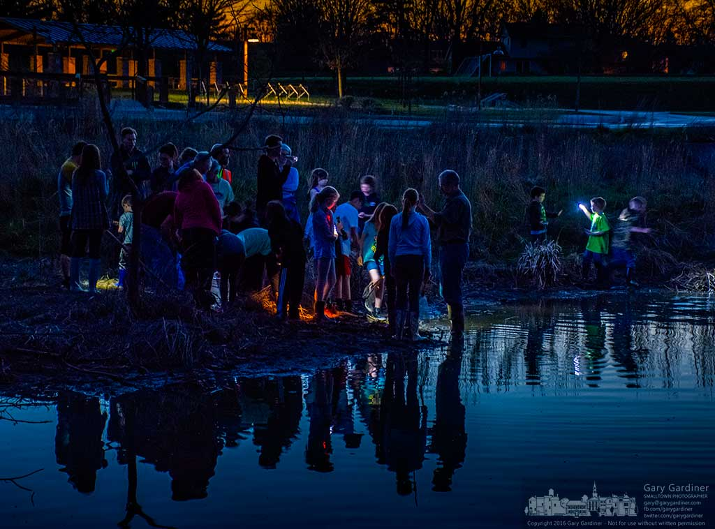 Mark Dilley, at center, shows toads, minnows, and small fish to children and their parents gathered for Frog Friday at the wetlands at sunset in Highlands Park. My Final Photo for April 15, 2016.