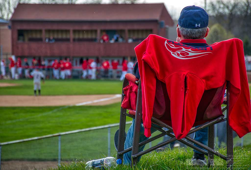 An Otterbein baseball fan sits in his chair at the apex of a small hill along the left field line at Fishbaugh Field during a game Wednesday. My Final Photo for April 13, 2016.