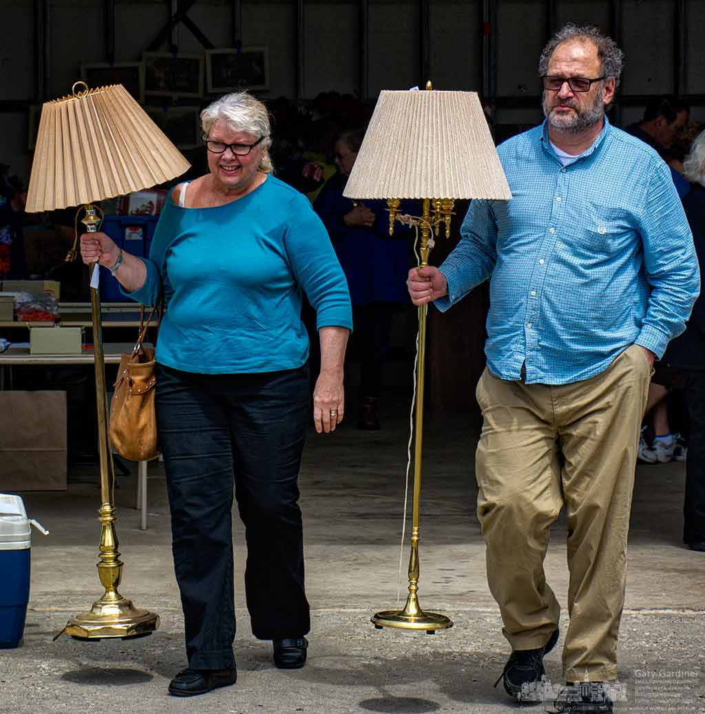 A couple carries away lamps they bought at the Senior Center garage sale Thursday in Westerville. y Final Photo for April 28, 2016.