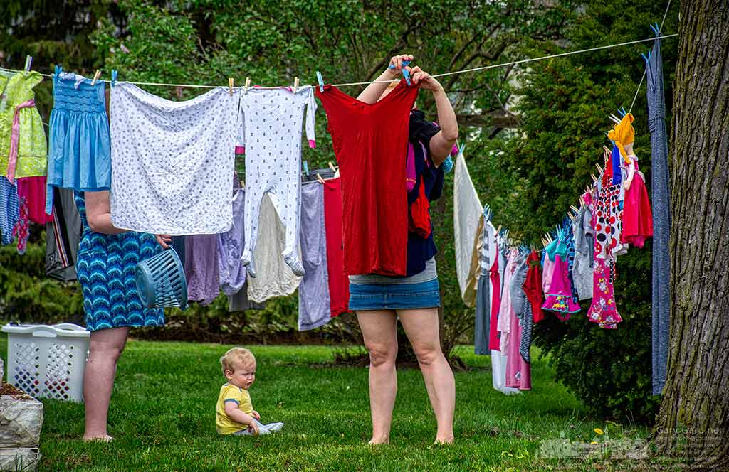 With her nine-month-old son playing in the grass and her pregnant friend at her side, a woman hangs her wash on a clothesline behind her house on East Home Street. My Final Photo for April 19, 2016.