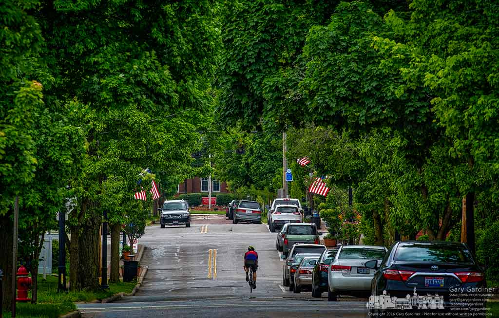 A bicyclist approaches State Street as he pedals alone on College Avenue during a break in afternoon traffic in Uptown Westerville. My Final Photo for May 18, 2016.