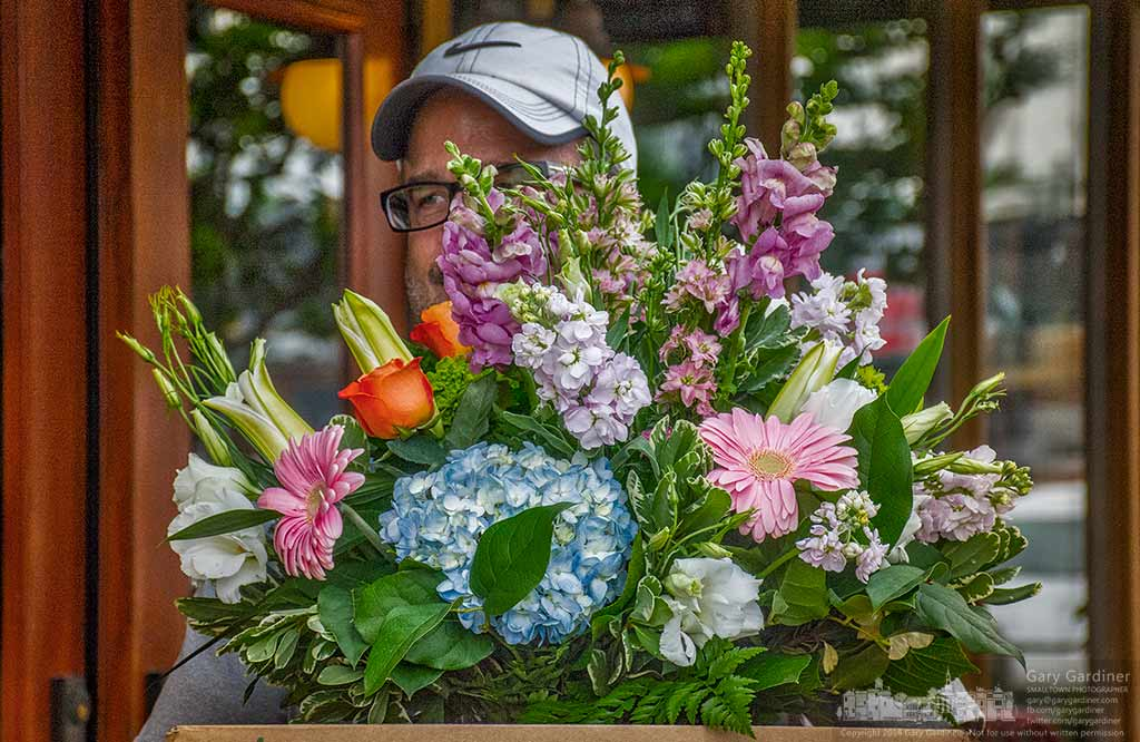 A man carries a box of flowers destined for Mothers Day gifts and centerpieces from a florist in Uptown Westerville. My Final Photo for May 7, 2016.
