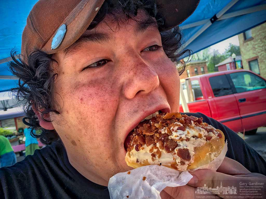 A cheese maker bites into a maple bacon iced creme-filled donut he bought from a baker at the Uptown Westerville Farmers Market. My Final Photo for May 11, 2016.