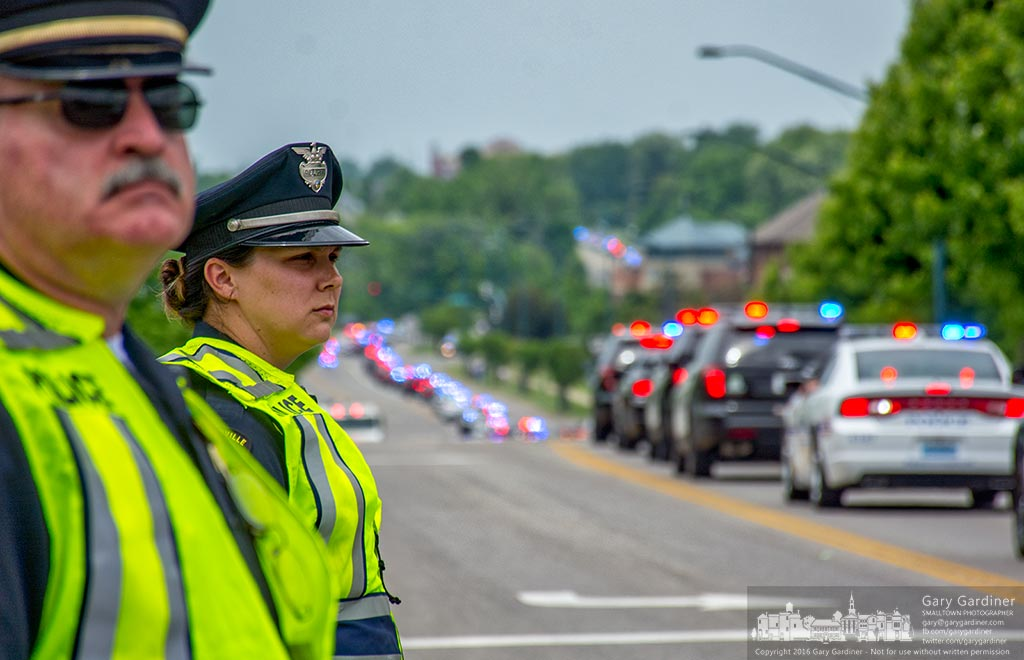 Westerville police officers regulate traffic at Africa and County Line roads as a procession of police cars and emergency vehicles leave St. Paul Catholic Church following funeral services for Hilliard Police Officer Sean Johnson. My Final Photo for May 25, 2016.