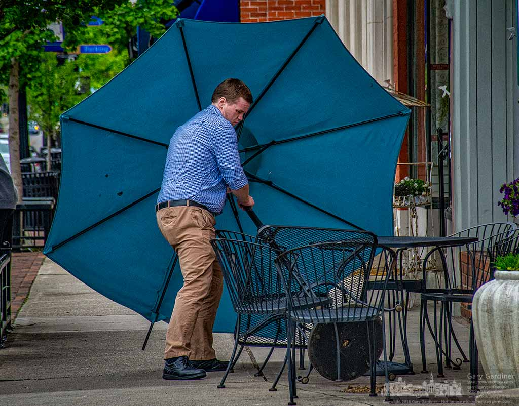 A passerby stops to right the umbrella in front of Heavenly Cup after it was toppled by the wind during an afternoon rain storm. My Final Photo for May 14, 2016.