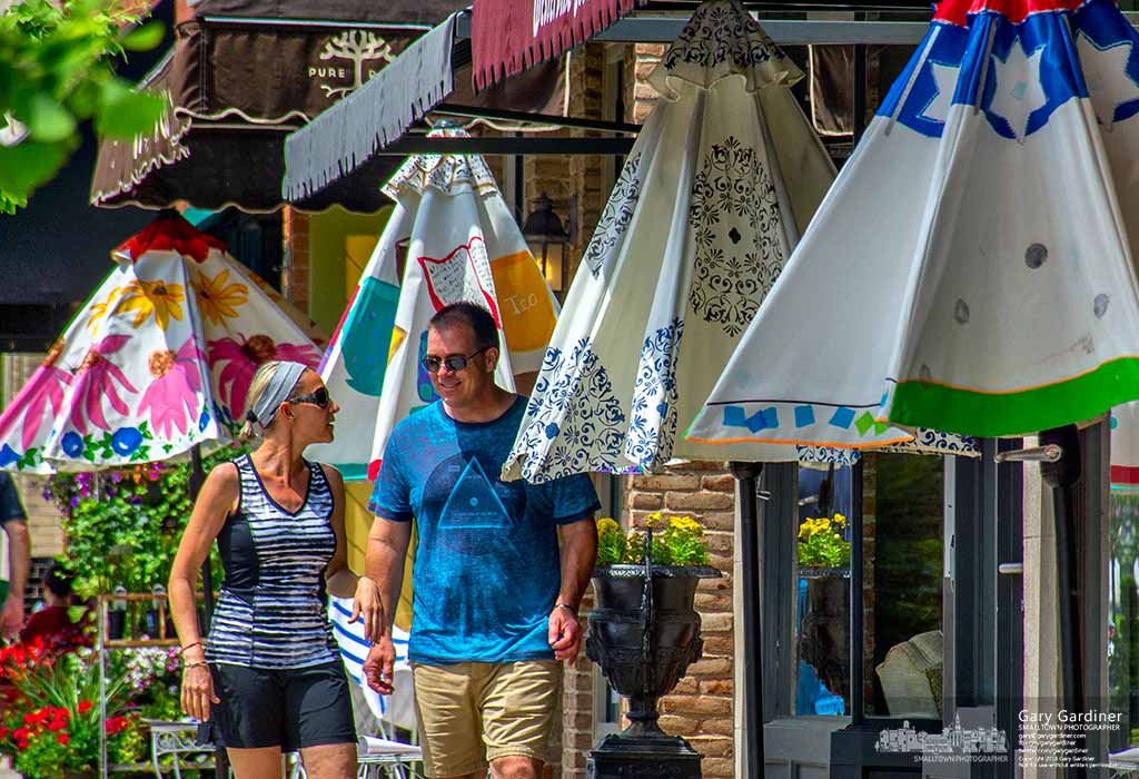 A couple walks past four of the one-of-a-kind artist's umbrellas displayed in Uptown Westerville before their auction next weekend. My Final Photo for May 29, 2016.