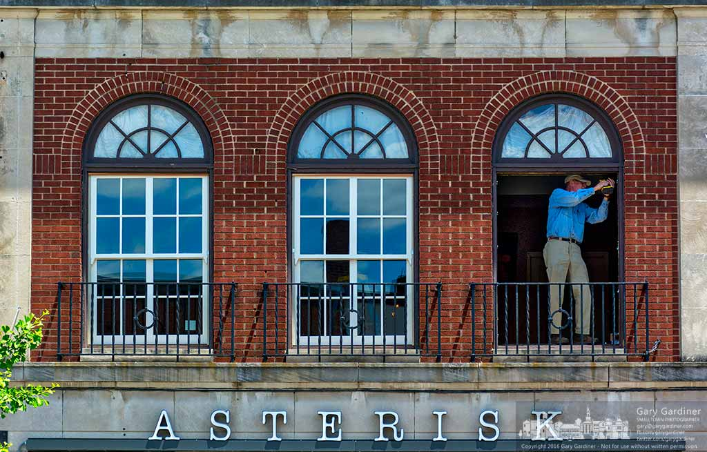 An installer places shims inside a window frame above Asterisk in Uptown Westerville before replacing the last of the three front windows in the building. My Final Photo for June 8, 2016.