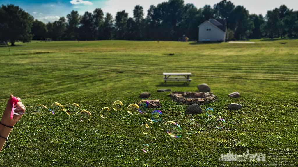 A young girl waves a bubble wand while her father grills the family dinner on Fathers Day in Johnstown, Ohio. My Final Photo for June 19, 2016.