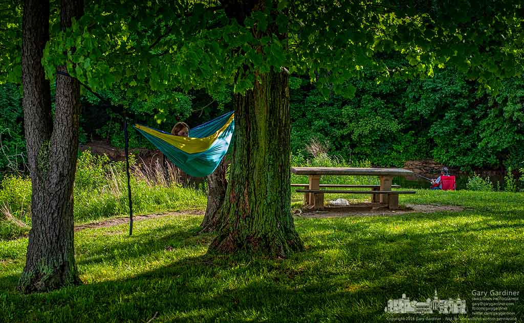A young woman relaxes in her hammock hung between trees at Red Bank Park as a fisherman tries his luck in the small lagoon formed by the small isthmus. My Final Photo for June 5, 2016.