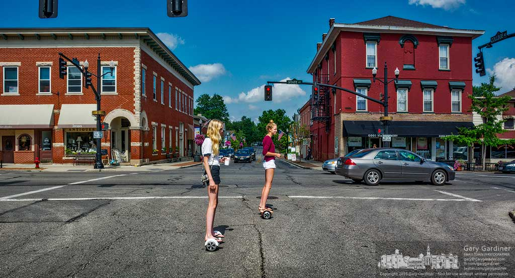 A pair of girls ride their hoverboards through the pedestrian crossing at West College and State Street in Uptown Westerville, Ohio. My Final Photo for June 23, 2016.