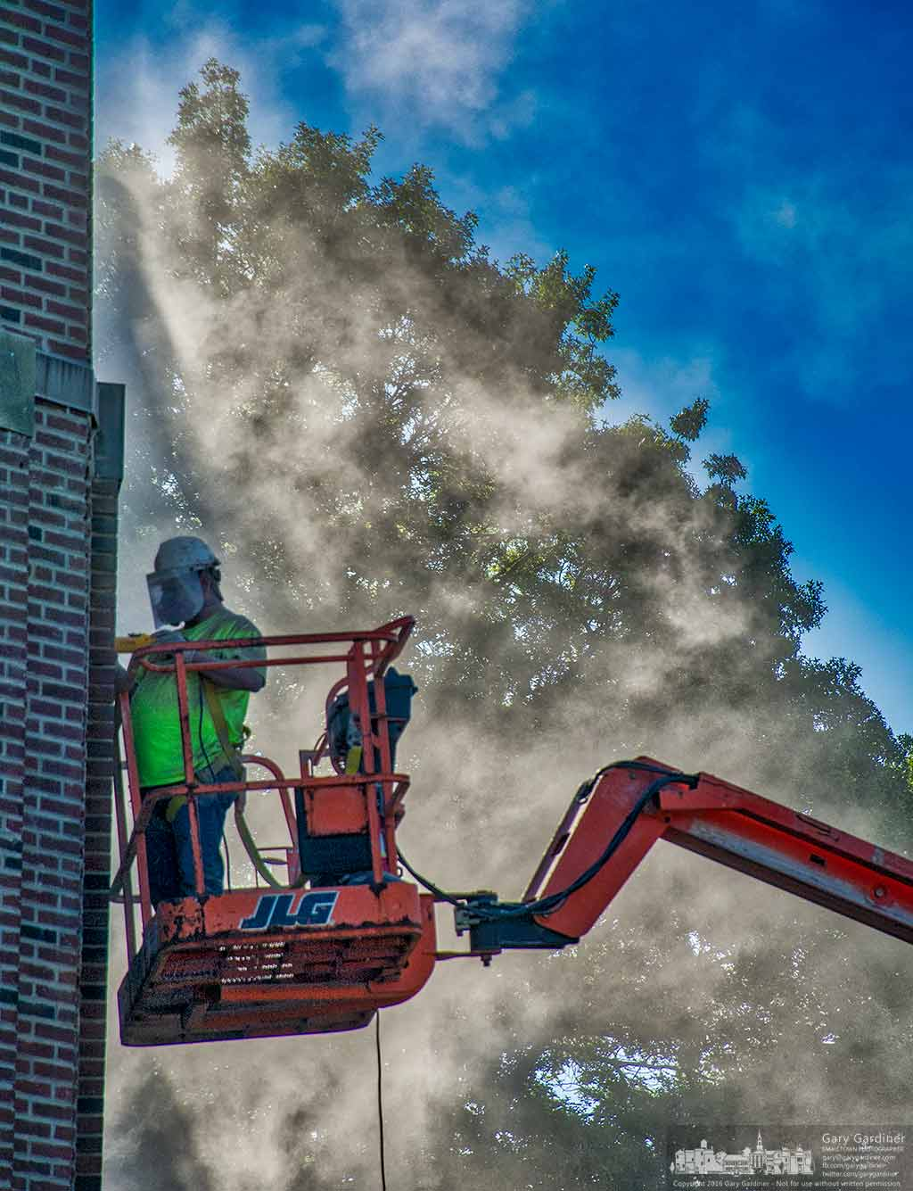 A worker grinds away mortar between bricks on the Battelle Fine Arts Center as part of the buildings renovation. My Final Photo for June 9, 2016.