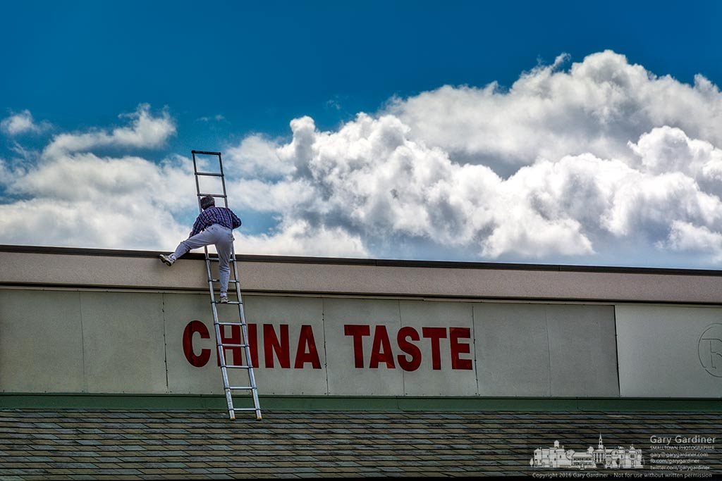 A China Gate restaurant worker carefully steps off a ladder resting on a lower roof to the top of the restaurant to make repairs. My Final Photo for July 9, 2016.
