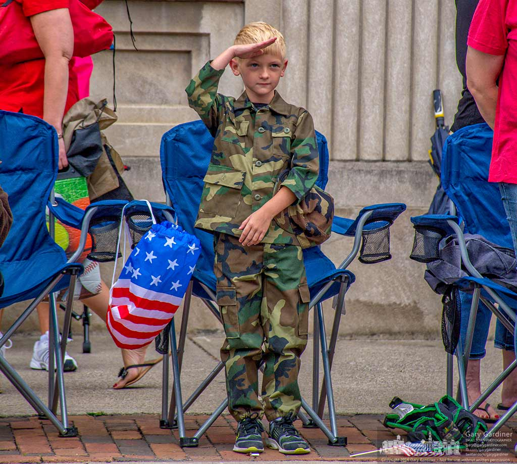 A youngster in a camo uniform stands and salutes as the Honor Guard leading the Independence Day parade passes by him in Westerville, Ohio. My Final Photo for July 4, 2016.