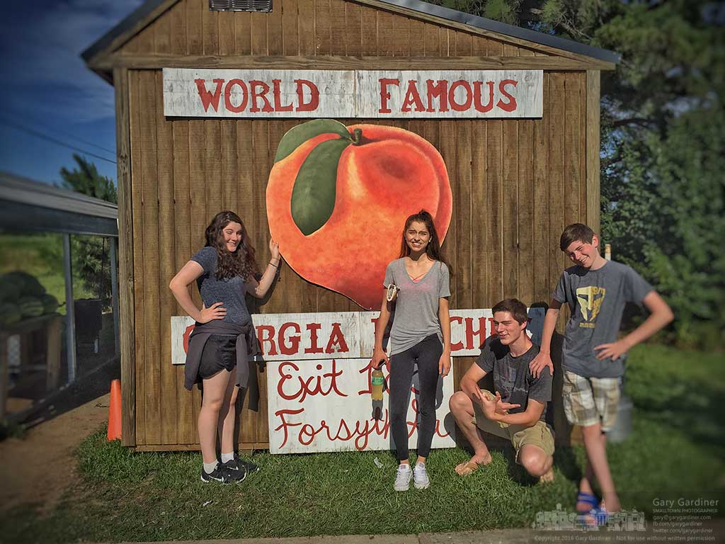 Four of the grandchildren stand in glaring morning sun for a photo at a Georgia peach roadside stand as they travel to Florida for a vacation. My Final Photo for July 15, 2016.