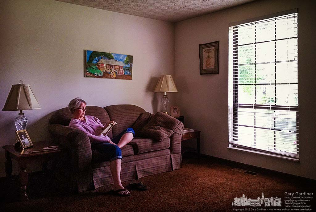 A woman reads a book in the glow of a warm August afternoon sun in the living room of her home in Westerville, Ohio. My Final Photo for August 27, 2016.