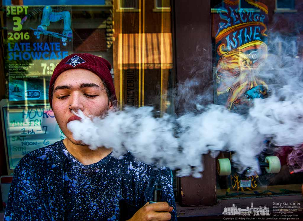 A skateboarder exhales smoke vapors after drawing on an electronic cigarette at OldSkool on East College in Uptown Westerville. My Final Photo for August 30, 2016.