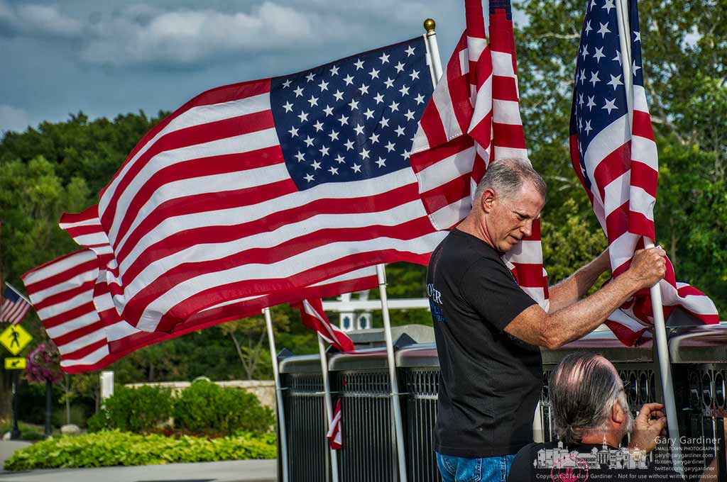 Retired Marine Steve Robbins hold a flag as retired Westerville fire fighter Tom Ullom fastens it to the railing along the Main Street bridge in preparation for Saturday's 9/11 Heroes Run. My Final Photo for Sept. 8, 2016.