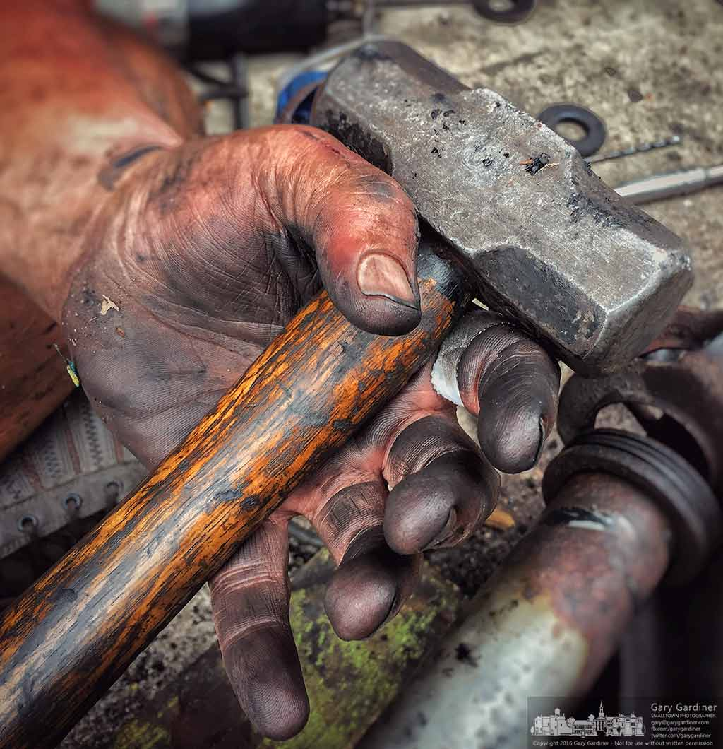 A mechanic holds a hammer in his grease-covered hands as he works on the front end suspension of his van. My Final Photo for Sept. 17, 2016.