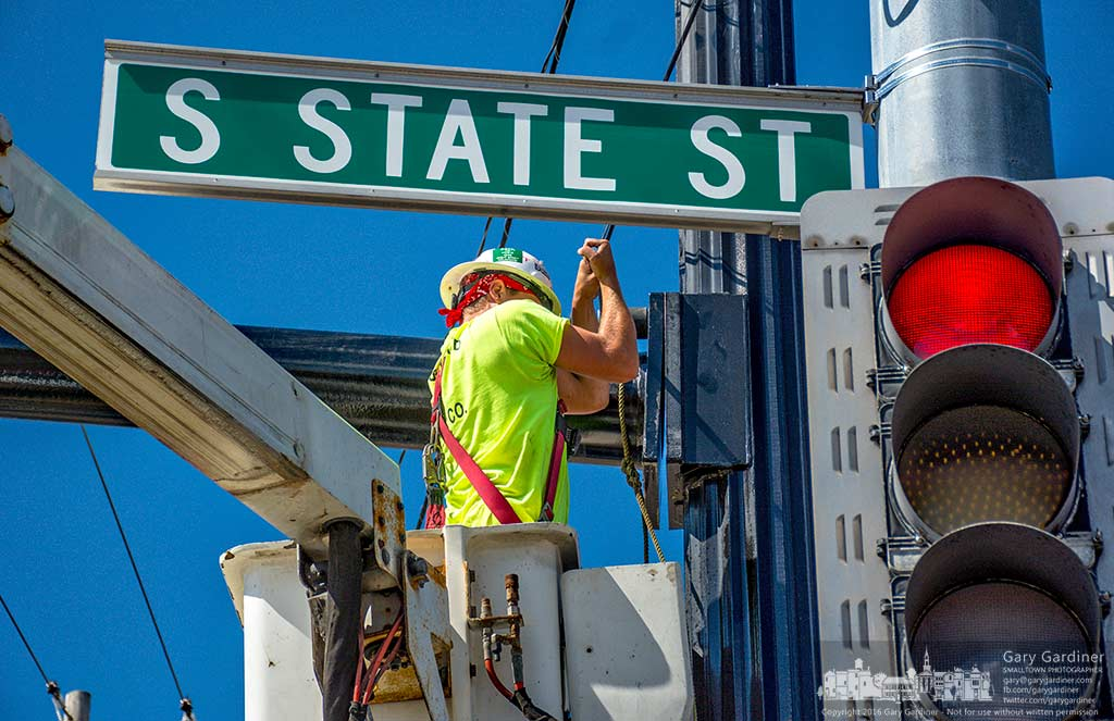 An electrical worker tightens bolts holding a traffic signal arm onto a pole at the corner of State and Schrock where the road is being widened and rebuilt. My Final Photo for Sept. 19, 2016.