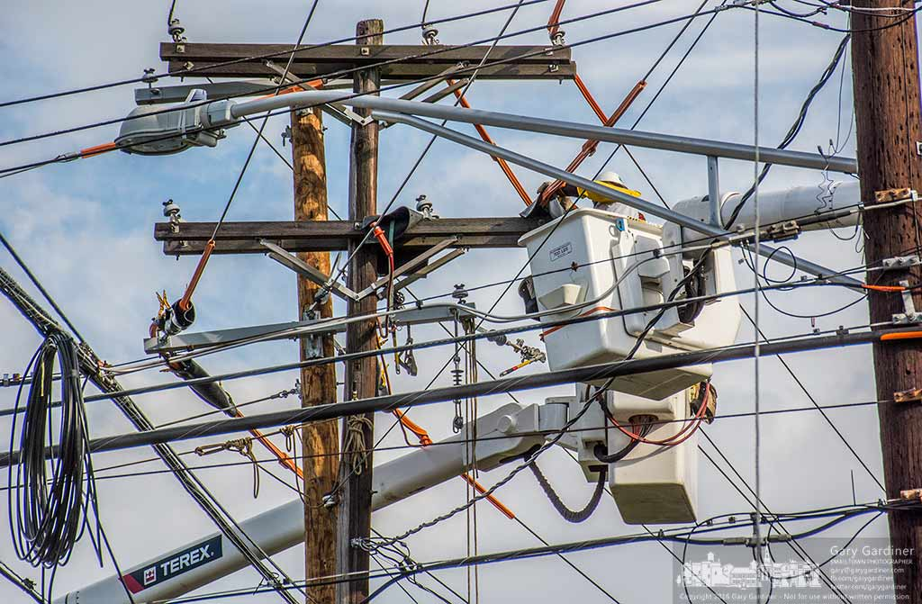 Westerville electrical workers transfer power lines from a rotting utility pole to a new pole inear a collection of power, cable, and telephone lines. My Final Photo for Sept. 29, 2016.