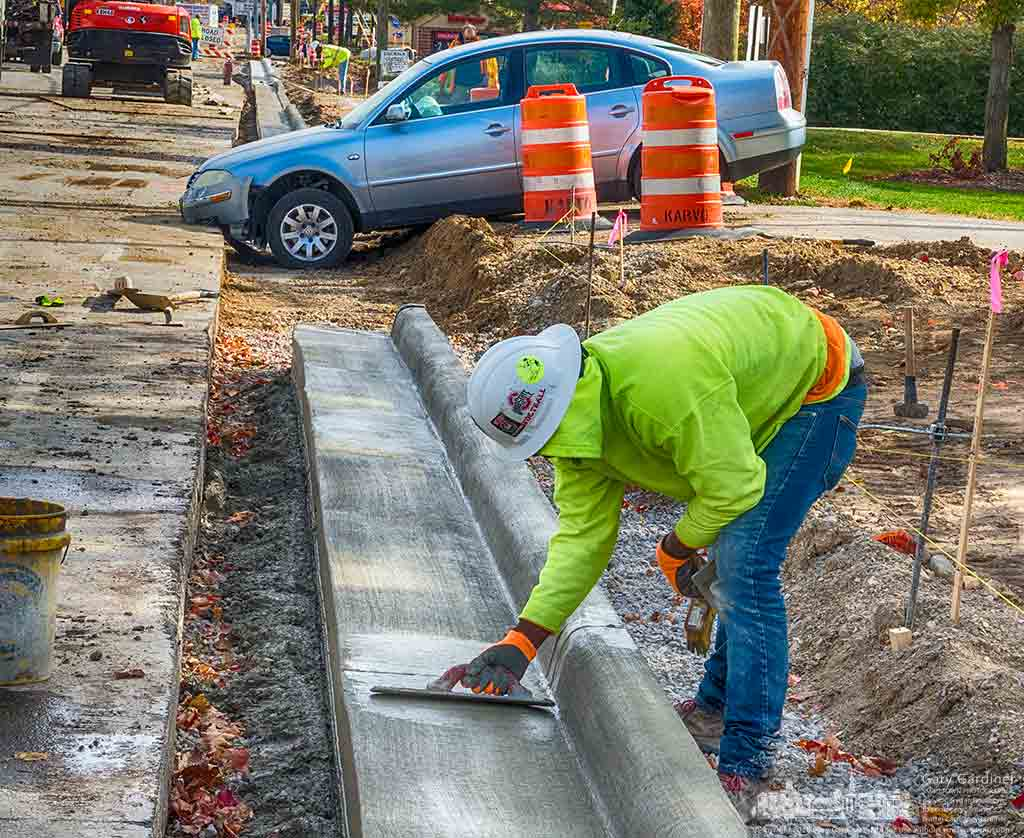 Contractor smooths concrete formed for a new curb on Schrock Road adjacent to a car that dropped into a construction trench after traveling past orange construction barrels. My Final Photo for Oct. 31, 2016.