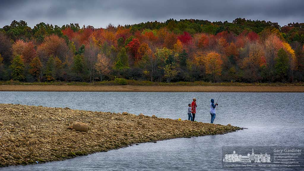 A family fishes from a point of land exposed from the lowered water level on Hoover Reservoir as the shoreline is brightened by the color of fall. My Final Photo for Oct. 30, 2016.