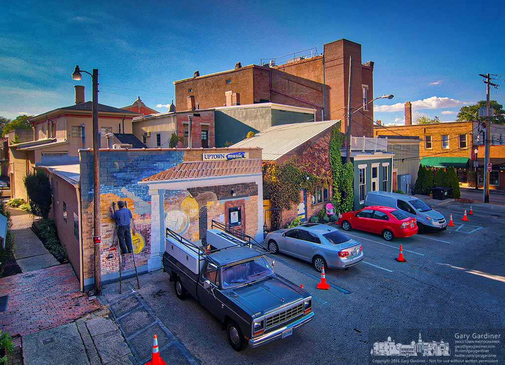 Artist Jim Saltz works into the evening hoping to complete this week the musical mural painted on the rear of Pure Roots and Uptown Music in Westerville, Ohio. My Final Photo for Oct. 3, 2016.