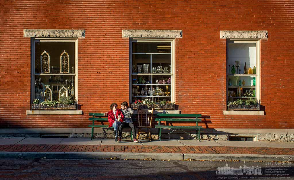 A couple sits on a bench outside Westerville Antiques enjoying a crisp fall afternoon in Uptown. My Final Photo for Nov. 10, 2016.