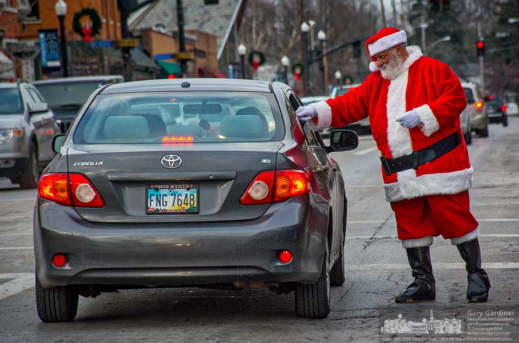 Santa Claus reaches into a car to deliver a peppermint candy cane to a youngster sitting in the rear seat of a car stopped at a traffic signal in Uptown Westerville. My Final Photo for Dec. 22, 2016.