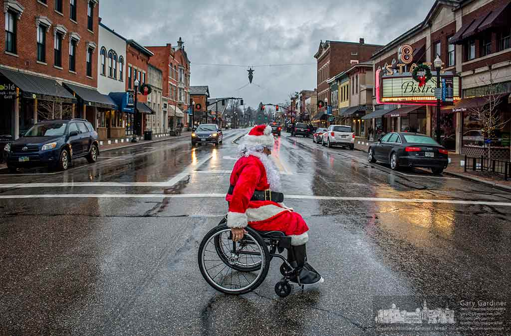 Santa Claus, portrayed by Fr. Joe Kovitch of , wheels his way across State Street in Uptown Westerville as he makes his way for morning coffee and to greet early morning shoppers. My Final Photo for Dec. 24, 2016.