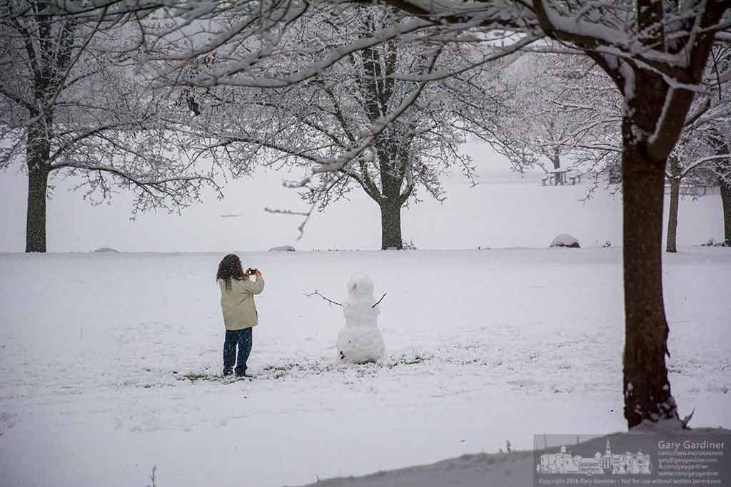 A woman pauses to photograph the snowman she and her family built from the fresh, wet snow at Alum Creek Park in Westerville. My Final Photo for Dec. 13, 2016.