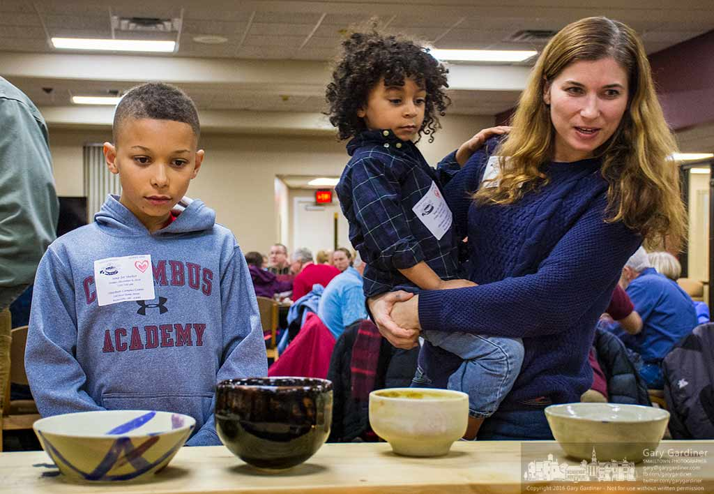 A mother and her children look over a selection of bowls from students at Columbus Academy as part of the Soup for Shelter fundraiser for Habitat for Humanity in Delaware County. My Final Photo for Dec. 9, 2016.