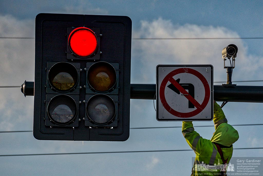 A worker removes the No Left Turn sign from the traffics signal in front of Kroger as contractors opened new lanes of traffic changing the flow of traffic on the busy roadway. My Final Photo for Dec. 19, 2016.