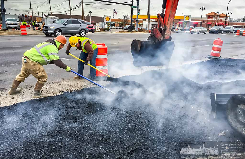 A road crew levels fresh asphalt laid on the southeast corner of State and Schrock filling a section of roadway removed during changes in the intersection. My Final Photo for Dec. 1, 2016.