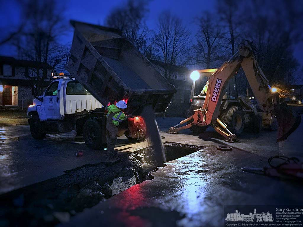 City work crews fill a hole at the end of a cul-de-sac after repairing a six-inch water main that sprung two leaks causing the road, sidewalks, and yards to bubble a rush of water. My Final Photo for Dec. 26, 2016.