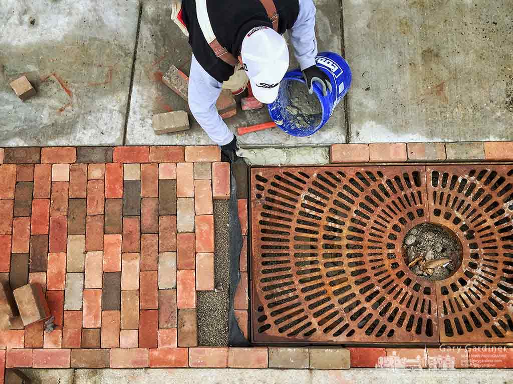 A bricklayer positions brick around a cast iron grate that will cover the area where trees will be planted in the sidewalk outside the Northstar Cafe in Uptown Westerville. My Final Photo for Jan. 11, 2017.