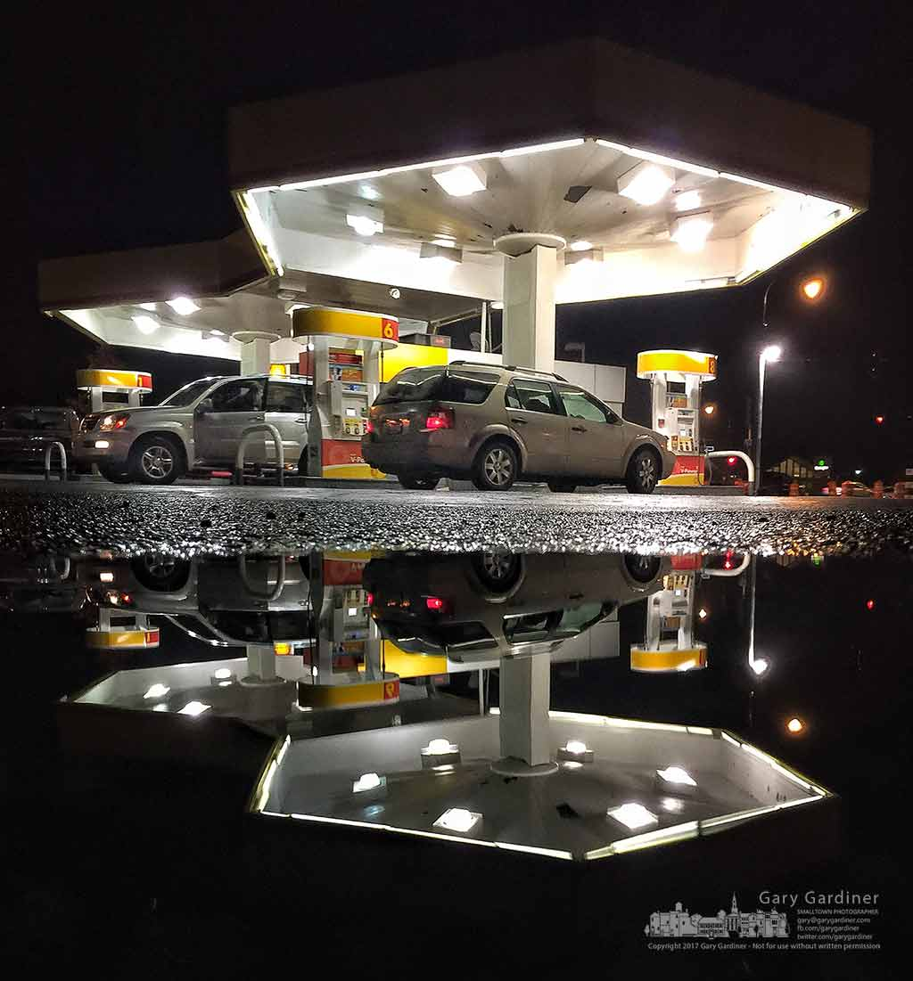 The nighttime lights of the Shell station at State and Schrock is reflected in a small puddle in the adjacent parking lot. My Final Photo for Jan. 14, 2017.
