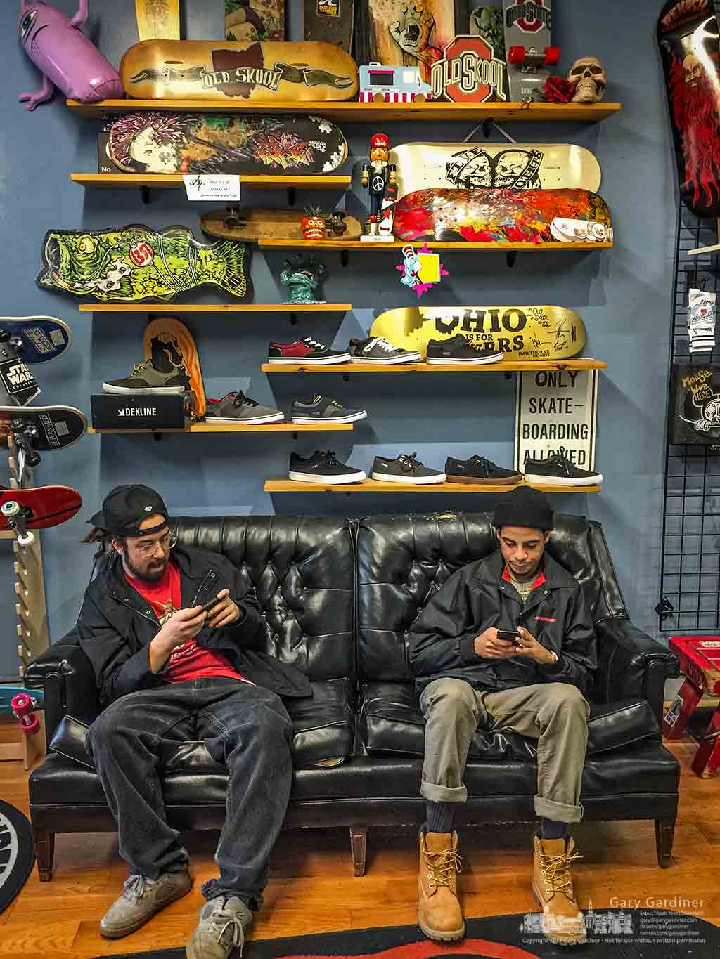 A pair of skateboarders check their smartphones from the couch in Old Skool Skateshop in Uptown Westerville as they wait for warmer and drier weather to spend time in the skate park. My Final Photo for Jan. 18, 2017.