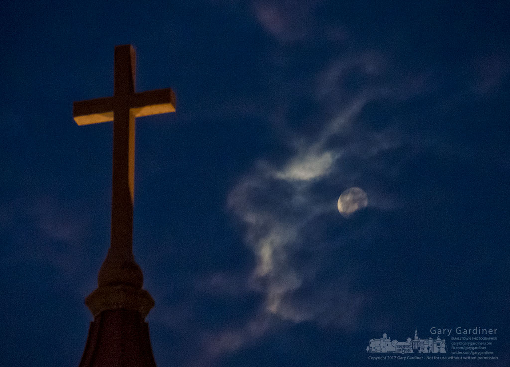 Early morning clouds slide past a near full moon behind a cross atop the old bell tower at St. Paul the Apostle Catholic Church in Westerville, Ohio. My Final Photo for Jan. 15, 2017.