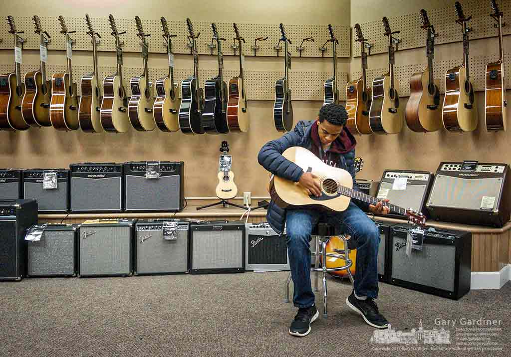 Thirteen-year-old Vaughn fingers the guitar he's chosen to be his first instrument after shopping with his parents at Music and Arts in Uptown Westerville. My Final Photo for Jan. 28, 2017.