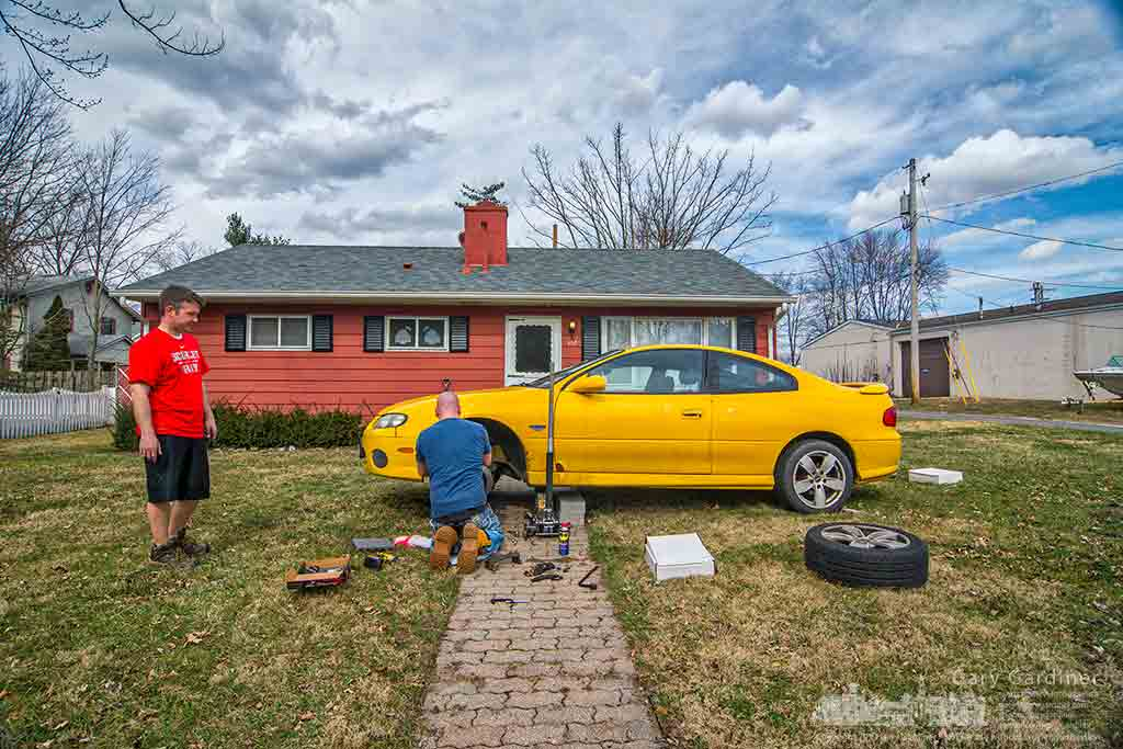 A man repairs the brakes on his car in the front yard of his home taking advantage of an unusually high late February temperature. My Final Photo for Feb. 24, 2017.