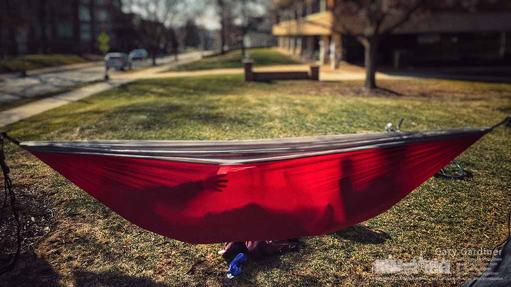 An Otterbein student gestures to her partner in a hammock hanging from trees on campus and Gove and Main in Westerville, Ohio. My Final Photo for Feb. 19, 2017.