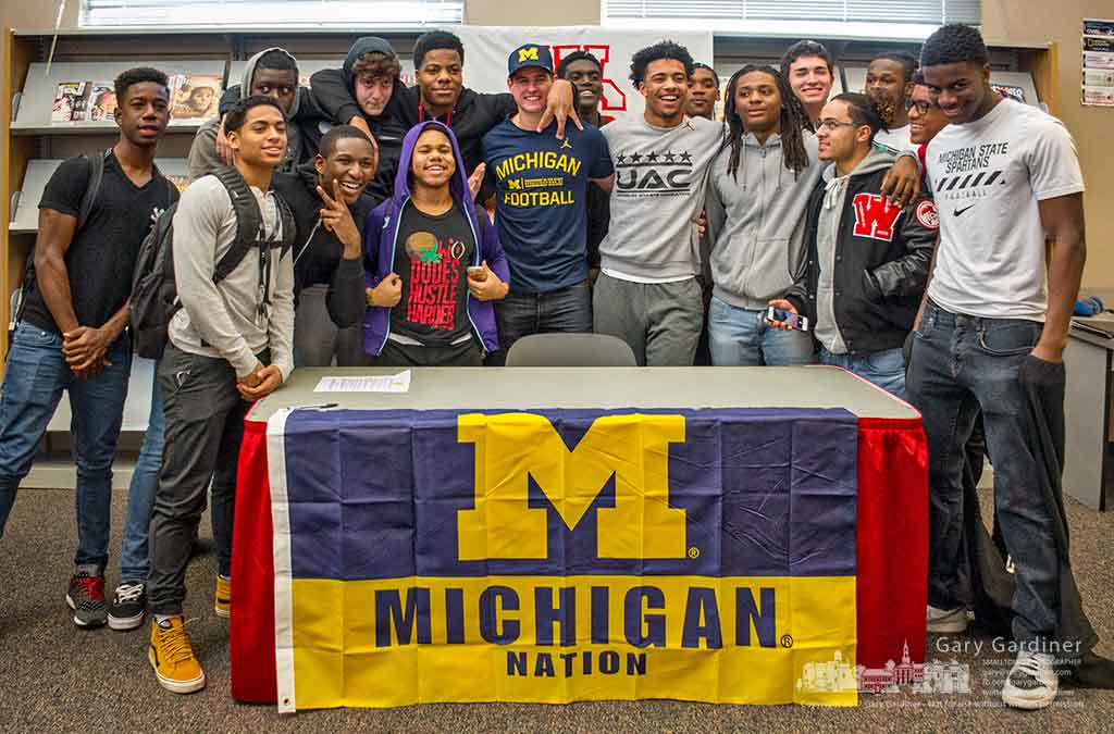 Westerville South punter Brad Robbins, center in Michigan shirt, is flanked by teammates after signing papers that will take him to Michigan for his college football career. My Final Photo for Feb. 6, 2017.