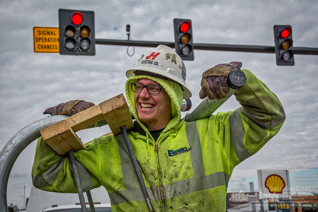 An electrician laughs at having his photo taken while he waits with his coworkers for the traffic signals to change at State and Schrock so he can carry his load of conduit and concrete forms to the opposite corner of the busy intersection. My Final Photo for Feb. 2, 2017.