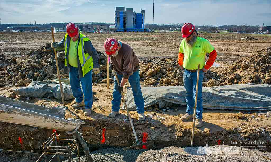 Three construction workers help settle concrete into footers being poured for the new COPC offices on Africa Road in Westerville. My Final Photo for March 9, 2017.