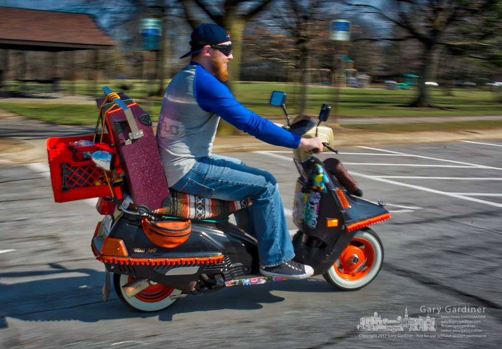Matt Witherstine rides his $250 scooter carrying a $350 Bluetooth speaker as he leaves Sharon Woods Park during a break on a warm early spring Friday. My Final Photo for March 24, 2017.
