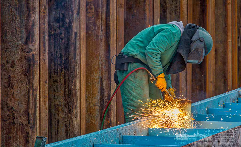 A welder cleans up sections of steel girders cut during the demolition of the Smothers Road bridge over Hoover Reservoir. My Final Photo for March 6, 2017.