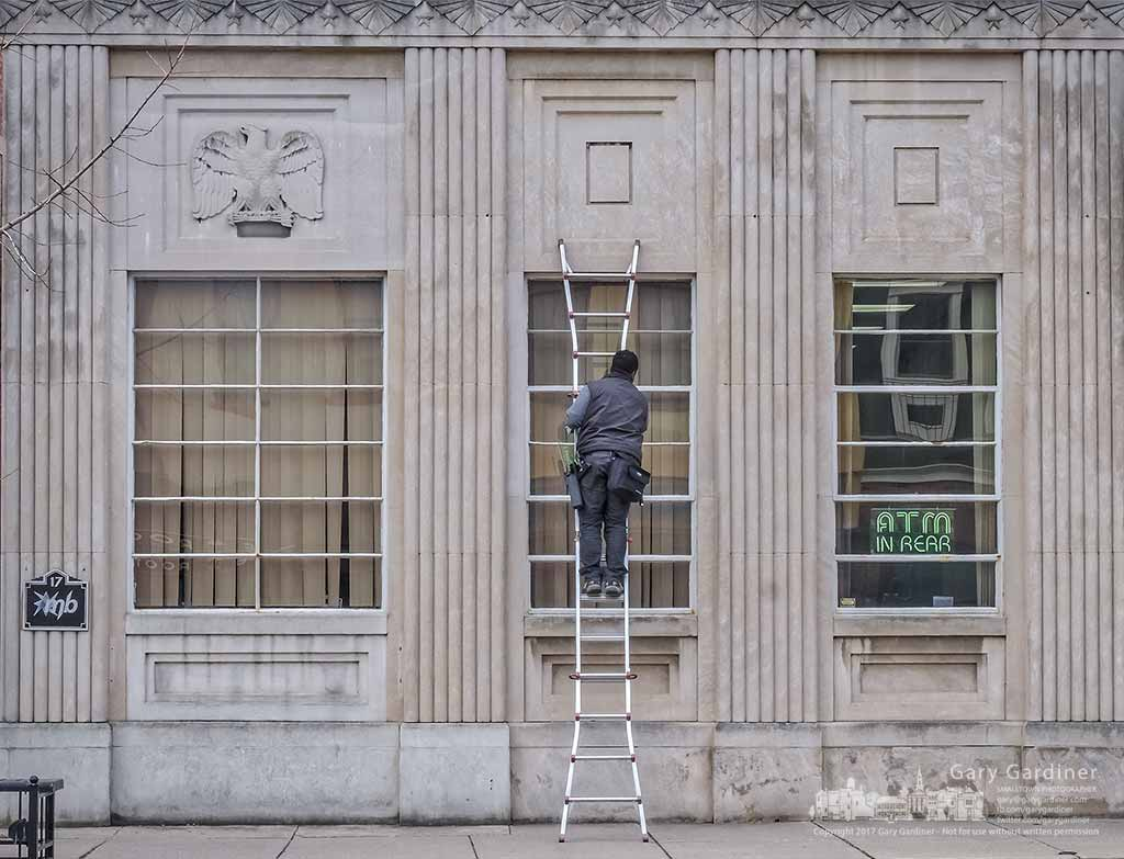 Window washer Micah reaches the halfway point of the tall bank of windows on the front of Middlefield Bank in Uptown Westerville. My Final Photo for March 21, 2017.